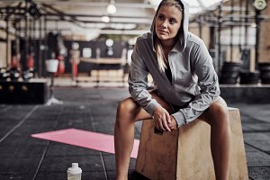 Fit young woman in sporstwear sitting in a gym smiling