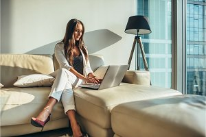 Elegant young female business woman using a laptop sitting on a sofa at home