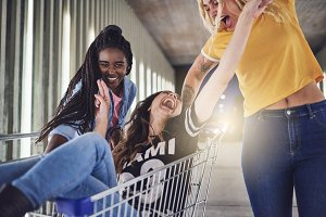 Carefree young girlfriends pushing each other in a shopping cart