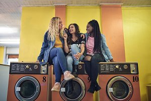 Laughing young girlfriends sitting on washing machines at a laundromat