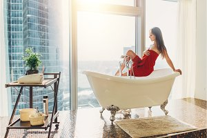 Slim young woman in towel sitting on bathtub in luxurious bathroom