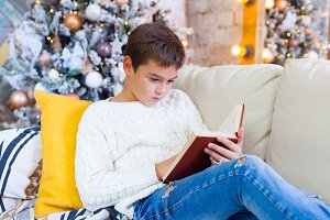boy 10 years on the couch reading a Christmas book. Xmas holiday concept