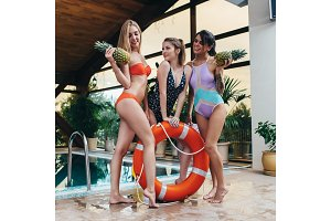 Three smiling female models posing in swimsuits with pineapples and lifebuoy ring at swimming-pool in luxurious hotel