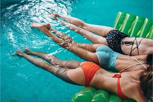 Three slim girlfriends wearing swimsuits lying on air mattress swimming in the swimming pool