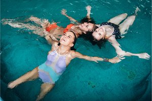 Funny female teenagers fooling around in the swimming pool laughing and enjoying their weekends