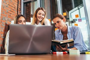 Three young girlfriends talking online lesson using a laptop sitting in a library