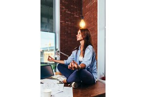 Side view of pretty creative female freelancer sitting in lotus pose on working desk under light bulb waiting for idea to come
