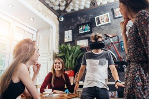 Group of young people having fun time together, cheerful guy wearing vr glasses in a cafe