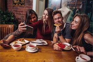 Group of cheerful young friends taking selfie with smartphone having light dinner in modern stylish restaurant
