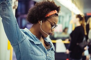 Young African woman listening to music on a subway train