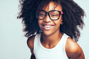 Laughing African girl in glasses standing against a gray background