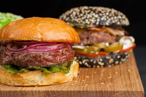 Closeup of set of three mini homemade Burger with marble beef and vegetables on a wooden Board