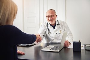 Mature doctor shaking hands with patient in office