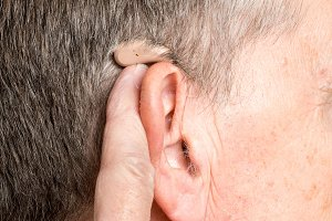 Close up of a tiny modern hearing aid behind ear