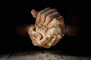 Hands of cook making dough