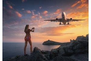 Beutiful woman makes photo of landing aircraft