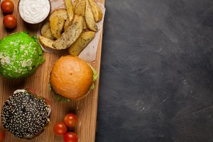 set of three mini homemade Burger with marble beef and vegetables on a wooden Board. the concept of junk food and fast food on dark concrete background. Top View with copy space