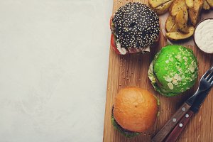 set of three mini homemade Burger with marble beef and vegetables on a wooden Board. the concept of junk food and fast food on light concrete background. Top View with copy space