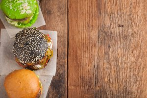 Set of three mini homemade Burger with marble beef and vegetables on a old wooden background. the concept of junk food and fast food. Top View with copy space