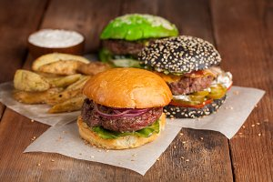 Set of three mini homemade Burger, Idaho potatoes with sauce and vegetables on a old wooden background. the concept of junk food and fast food