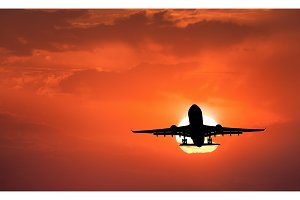 Silhouette of landing aircraft and red sky with sun