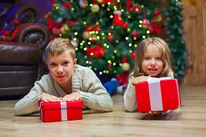 children lie near Christmas Present In Front Of Tree