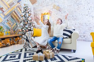 Two children a boy and a girl at a Christmas tree on a sofa with gifts. In light colors. throw up gifts