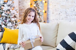 Happy little smiling girl with christmas gift box