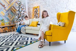 A 10-year-old girl sits on a yellow chair in the house before the Christmas holidays. In the background a boy is sitting on the couch