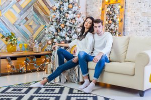 Happy couple of lovers sitting on the bed. Christmas interior. Lovers together