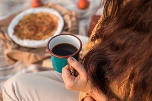 Cozy autumn picnic. Female hand holding a mug with tea