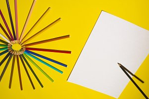 Multicolour pencils and sheet of paper on yellow background. Art and creativity concept