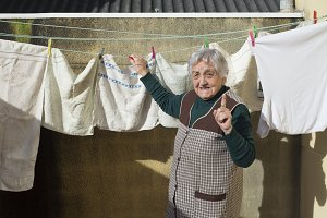 Elderly woman hanging out washing