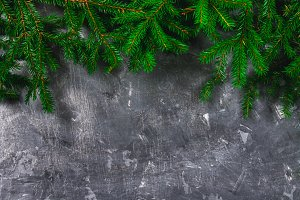 Spruce New Year's branches on top of a gray concrete background. New Year Christmas. Free space for text.