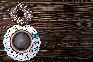 Coffee cup and donut on wooden table