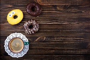 Coffee cup and donuts on wooden tabl