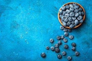 Blueberries in bowl on blue backgrou