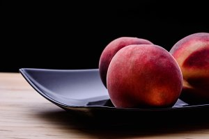 Tasty peaches on dark plate