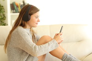 teen listening to music on a sofa