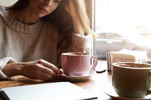 Cropped portrait of young woman drinking coffee, during work break