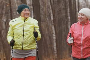 Nordic walking for elderly women outdoor - two happy senior ladies have training outdoor
