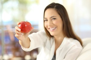 Happy woman offering an apple