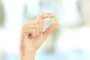 woman hand holding a yellow pill
