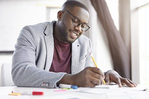 Smiling dark skinned male enterpreneur writes notes in notepad, sits at coworking space. African company manager writes information on blank sheet of notebook, creates reminder in calendar, makes list