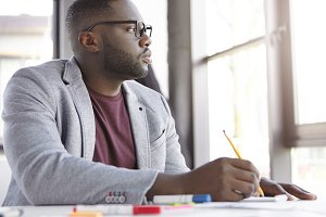 Serious dark skinned plump male businessman, studies important documents, thinks how complete online project, looks pensively aside, generates new ideas, writes down general concepts in notebook