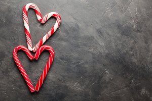 Peppermint Candy Canes in Heart Shapes on black concrete background. Christmas background. top view with copy space