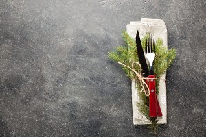 Christmas table. Cutlery with wooden handles and with a sprig of fir tied with string on a dark concrete background with copy space. Photo is decorated with snowflakes. Top view