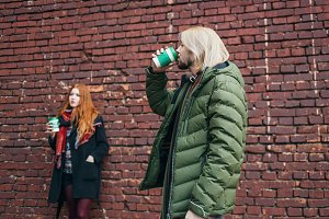 holidays, winter, hot drinks, fashion and people concept - happy couple of tourists in warm urban clothes drinking coffee from disposable cups in old town, brick wall background