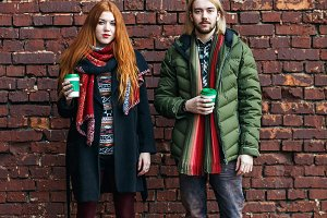 Hot drinks, winter, holidays, fashion and people concept - happy couple of tourists in warm urban clothes standing with coffee disposable cups on brick wall urban background.