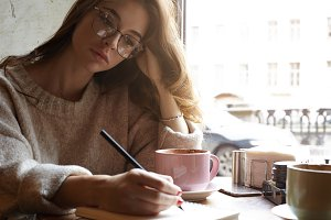 Gorgeous Caucasian hipster young woman in glasses plans her day